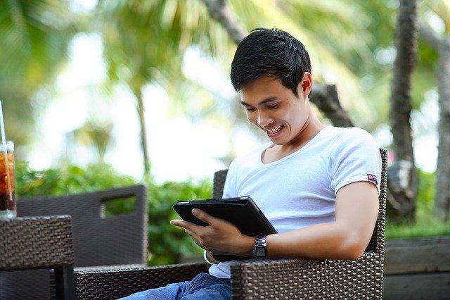 man smiling at tablet