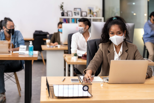 a lady sitting at her office desk wearing a mask while using her laptop